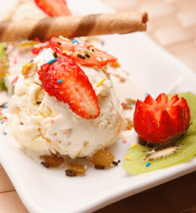 Vanilla ice cream with rolled cookies and strawberries