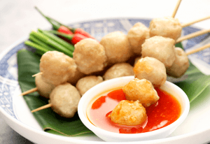Fried tofu balls on bamboo skewers with red dipping sauce.